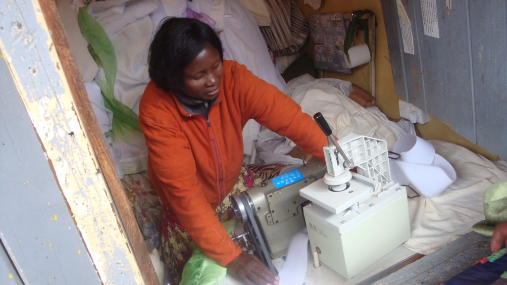 Eunice Nambusi shows us how to use her tailoring machine that punches holes in curtains in her business space in Kibera, Nairobi